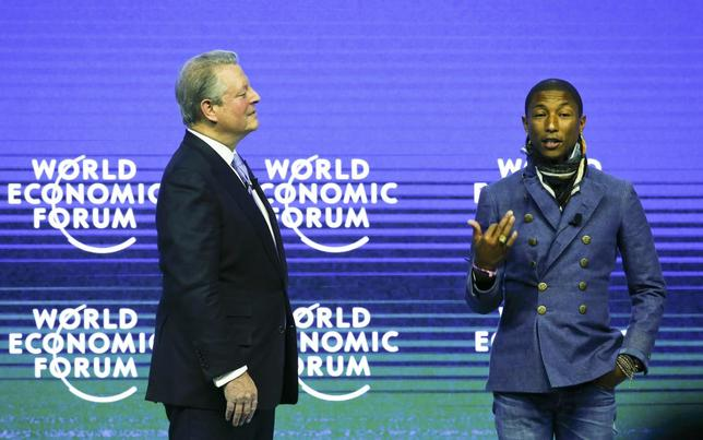 Nobel Peace Prize laureate Al Gore (L), former U.S. Vice-President and Chairman and Co-Founder of Generation Investment Management listens to singer Pharrell Williams, Creative Director and Brand Ambassador of Bionic Yarn at the What's Next? A Climate for Action event in the Swiss mountain resort of Davos January 21, 2015. REUTERS/Ruben Sprich