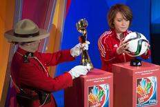 A member of the Royal Canadian Mounted Police  carries the FIFA Women's World Cup trophy along with West Ottawa Soccer Club player Talia Laroche who carries the Official Match Ball as part of the preliminary activities surrounding the official draw for the FIFA Women's World Cup Canada 2015 at The Canadian Museum of History. Mandatory Credit: Marc DesRosiers-USA TODAY Sports
