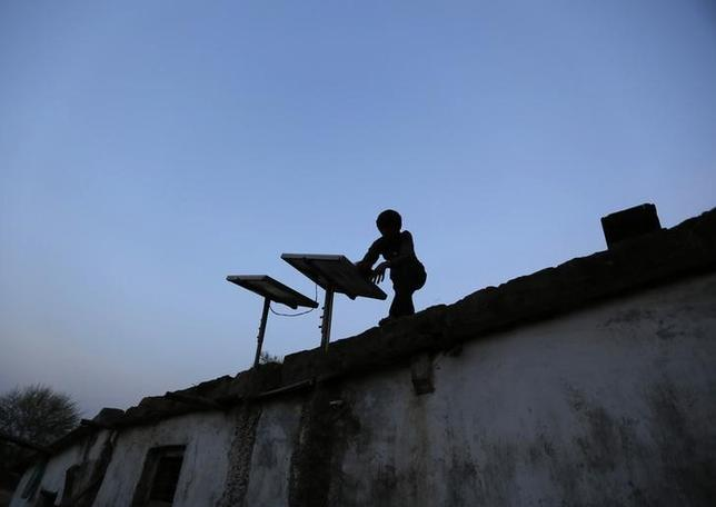 A boy dusts off a solar panel installed on the rooftop of his house on the outskirts of Ahmedabad October 27, 2014. REUTERS/Amit Dave/Files