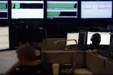 Spécialistes de la cybersécurité assurant le suivi du trafic internet dans un centre situé en Virginie. Désormais considéré comme un champ de confrontation à part entière et un enjeu économique, le cyberespace est aujourd'hui indissociable des théâtres de guerres dites traditionnelles mais ses limites demeurent floues, estiment les analystes. /Photo d'archives/REUTERS/Jonathan Ernst