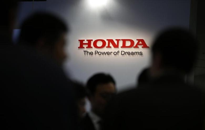 A logo of Honda Motor Co is seen behind journalists after the unveiling event for the company's all-new hybrid sedan ''Grace'' in Tokyo December 1, 2014. REUTERS/Toru Hanai/Files