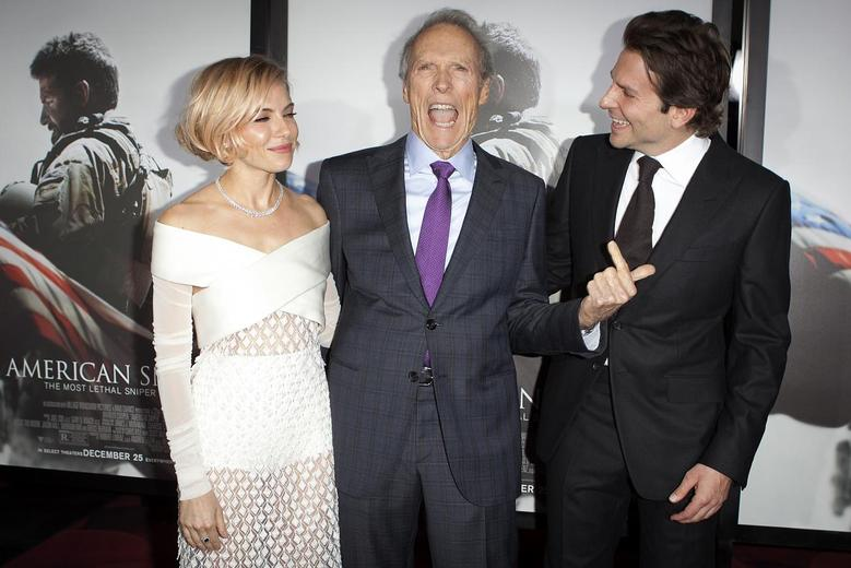 Actress Sienna Miller (L), director Clint Eastwood and actor Bradley Cooper ( R) arrive for the premiere of the film ''American Sniper'' in New York, December 15, 2014.  REUTERS/Carlo Allegri