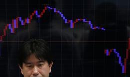 Работник трейдинговой компании на фоне экрана с графиком динамики пары иена/евро. Токио, 26 января 2015 года. Азиатские фондовые рынки завершили торги понедельника разнонаправленно под влиянием итогов парламентских выборов в Греции и местных событий. REUTERS/Yuya Shino