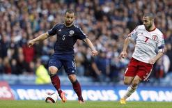 Scotland's Shaun Maloney is challenged by Georgia's Jaba Kankava (R) during their Euro 2016 qualification soccer match at the Ibrox Stadium in Glasgow, Scotland October 11, 2014. REUTERS/Russell Cheyne