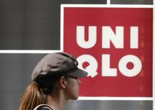 A woman walks past a logo of casual clothing store Uniqlo operated by Japan's Fast Retailing in Tokyo July 9, 2009. REUTERS/Issei Kato