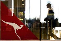 A passenger walks past a Qantas Airways emblem at the Sydney International Airport terminal July 18, 2014. REUTERS/David Gray