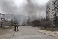 Украинские военные у здания, горящего после обстрела, в Мариуполе. 24 января 2015 года. Кровавая атака на находящийся под украинским контролем портовый Мариуполь в прошлую субботу была военным преступлением, поскольку, как сказал в понедельник высокопоставленный чиновник ООН, ее мишенью специально были избраны мирные жители. REUTERS/Nikolai Ryabchenko
