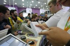 Люди покупают  iPhone 6 в Москве 26 сентября 2014 года. Российская компания Inventive Retail Group, объединяющая магазины, продающие по франшизе продукцию Apple и Samsung, увеличила продажи на 67 процентов до 9,4 миллиарда рублей в четвертом квартале на фоне ажиотажного спроса в конце года, когда покупатели старались потратить стремительно дешевеющий рубль и закупались впрок. REUTERS/Maxim Shemetov