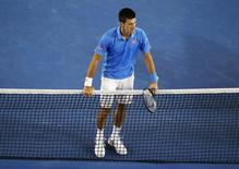 Novak Djokovic of Serbia leans on the net after defeating Milos Raonic of Canada in their men's singles quarter-final match at the Australian Open 2015 tennis tournament in Melbourne January 28, 2015. REUTERS/Carlos Barria