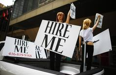 """Motorized mannequins hold signs that read """"Hire Me"""" in Toronto May 23, 2014. Canada's economy unexpectedly shed 28,900 jobs in April, mainly due to steep declines in full-time employment and in the private sector, Statistics Canada data indicated earlier this month.    REUTERS/Mark Blinch"""