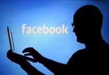 Мужчина с ноутбуком на фоне экрана с логотипом Facebook. Зеница, 14 августа 2013 года. Facebook Inc сообщил в среду об увеличении выручки в прошлом квартале в полтора раза за счет роста мобильной рекламы в крупнейшей в мире социальной сети. REUTERS/Dado Ruvic