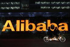 Personas pasan en una bicicleta doble frente el logo de Alibaba en la sede de la compañía en Hangzhou. Imagen de archivo, 10 noviembre, 2014. Alibaba Group Holding Ltd reportó el jueves ingresos trimestrales que no cumplieron con las expectativas del mercado, mostrando señales de una desaceleración en el arrollador crecimiento del gigante chino del comercio electrónico. REUTERS/Aly Song