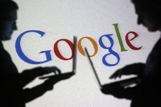 Personas posan con computadores portátiles frente a una pantalla que proyecta el logo de Google, foto tomada en Zenica, 29 de octubre de 2014.  Los ingresos de Google Inc crecieron un 15 por ciento en los últimos tres meses del 2014, por debajo de las expectativas de Wall Street, en un trimestre en el que el precio de sus anuncios publicitarios en internet siguió bajo presión. REUTERS/Dado Ruvic