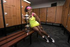 Serena Williams of the U.S. poses with the women's singles trophy in the players' locker room after she defeated Maria Sharapova of Russia at the Australian Open tennis tournament in Melbourne January 31, 2015.   REUTERS/Fiona Hamilton/Tennis Australia/Handout via Reuters