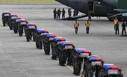 Members of the Philippine National Police's (PNP) Special Action Force (SAF) unit carry metal caskets containing the bodies of slain SAF police who were killed in Sunday's clash with Muslim rebels, upon arriving at Villamor Air Base in Pasay city, metro Manila January 29, 2015.  REUTERS/Romeo Ranoco
