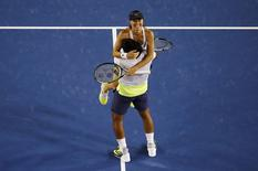 Martina Hingis (top) of Switzerland hugs Leander Paes of India as they celebrate defeating Kristina Mladenovic of France and Daniel Nestor of Canada to win their mixed doubles final match at the Australian Open 2015 tennis tournament in Melbourne February 1, 2015. REUTERS/Carlos Barria