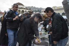 """El nuevo gobierno griego reveló el domingo sus planes para elevar el salario mínimo, continuando con el retroceso en las políticas de austeridad impuestas tras el rescate internacional, poniendo de relieve los malabarismos a los que se enfrenta el ejecutivo de Tsipras para persuadir a Europa de que firme un nuevo acuerdo de deuda. En la imagen, una cola para recibir sopa en un comedor social organizado por el grupo """"O Allos Anthropos"""" (""""El Otro Humano"""") en Atenas, el 20 de enero de 2015. REUTERS/Marko DjuricaRTR4M5TF"""