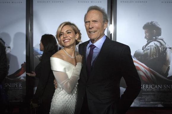Actress Sienna Miller (L) and director Clint Eastwood arrive for the premiere of the film ''American Sniper'' in New York, December 15, 2014.  REUTERS/Carlo Allegri
