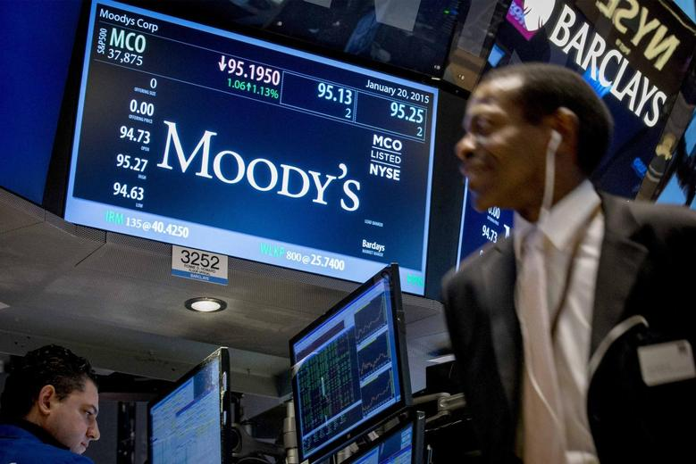 A screen displays Moody's ticker information as traders work on the floor of the New York Stock Exchange January 20, 2015. REUTERS/Brendan McDermid