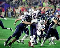 Feb 1, 2015; Glendale, AZ, USA; Seattle Seahawks defensive end Michael Bennett (72) tackles New England Patriots quarterback Tom Brady (12) during the third quarter in Super Bowl XLIX at University of Phoenix Stadium. Matt Kartozian-USA TODAY Sports