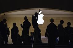 A man talks on his telephone as customers walk through an Apple store in Grand Central Terminal in New York, March 15, 2013.  REUTERS/Lucas Jackson