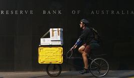 Мужчина проезжает мимо здания Резервного банка Австралии в Сиднее 2 апреля 2013 года. Австралийский Центробанк во вторник сократил ставку до рекордного минимума 2,25 процента годовых, прервав 18-месячный перерыв в осуществлении стимулов, пытаясь подстегнуть экономику, одновременно сохраняя понижательное давление на местный доллар. REUTERS/Daniel Munoz