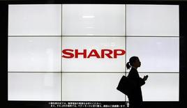 Женщина проходит мимо логотипа Sharp Corp на вокзале в Токио. 6 марта 2013 года. Японский производитель электроники Sharp Corp заявил во вторник, что получит чистый годовой убыток - в третий раз за последние четыре года. REUTERS/Yuya Shino