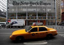 Un taxi pasa a las afueras de las oficinas del diario New York Times en Times Square, feb 7 2013. New York Times Co reportó ingresos y ganancias trimestrales superiores a lo esperado, ya que una mayor suscripción digital y ventas de publicidad contrarrestaron en gran parte una caída en los ingresos por anuncios impresos.   REUTERS/Carlo Allegri