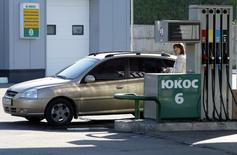 Una mujer cargando combustible en una gasolinera de Yukos en Moscú, jul 8 2004. Los traumas de un colapso de los precios del petróleo que está presionando a la economía y de las sanciones occidentales que afectan a compañías energéticas no evitarán que Rusia mantenga la producción petrolera cerca de un máximo récord este año, según empresas, funcionarios y analistas. REUTERS/Viktor Korotayev
