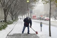 A worker clears the street under the first winter snowfall in Washington January 6, 2015. REUTERS/Yuri Gripas