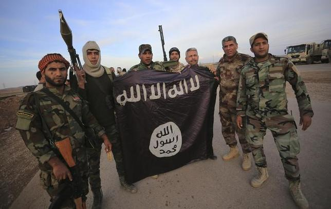 Iraqi Shi'ite fighters pose with an Islamic State flag which they pulled down on the front line in Jalawla, Diyala province, November 23, 2014.  REUTERS/Stringer/Files