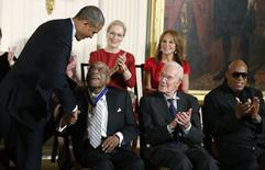 U.S. President Barack Obama presents a Presidential Medal of Freedom to golfer Charles Sifford (front L) as fellow recipients economist Robert Solow (2nd R), singer Stevie Wonder (R), actress Meryl Streep (C-Rear) and actress Marlo Thomas (R-Rear) applaud during a ceremony in the East Room of the White House in Washington, in this November 24, 2014 file photo. REUTERS/Larry Downing/Files