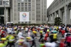Thousands of runners fill the street in front of the Tokyo Metropolitan Government Building bearing a banner promoting the 2020 Tokyo Olympics at the start of the Tokyo Marathon in this February 23, 2014 file photo. REUTERS/Franck Robichon/Pool/Files