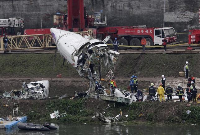 Emergency teams remove pieces of wreckage at the site of the crashed TransAsia Airways plane Flight GE235 in New Taipei City February 5, 2015.  REUTERS/Pichi Chuang