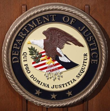 The Department of Justice logo is seen on the podium during a news conference in New York January 23, 2013. REUTERS/Carlo Allegri