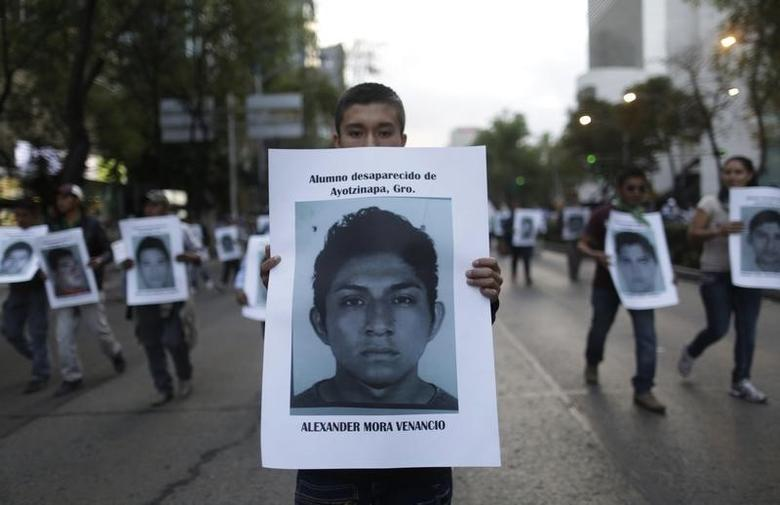 A demonstrator carries a photograph of Alexander Mora Venancio, one of the 43 missing trainee teachers, during a march in support of the students in Mexico City December 6, 2014. REUTERS/Carlos Jasso