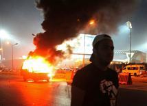 Футбольный болельщик у горящей полицейской машины рядом со стадионом близ Каира. 8 февраля 2015 года. Двадцать два человека погибли в воскресенье при попытке зайти на футбольный стадион в Каире, куда их не пропустили правоохранительные органы, сообщила прокуратура. REUTERS/Stringer