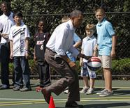 U.S. President Barack Obama dribbles the ball past some children while doing some basketball drills, during the annual Easter Egg Roll at the White House in Washington, in this April 25, 2011 file photograph.  REUTERS/Jim Young/Files