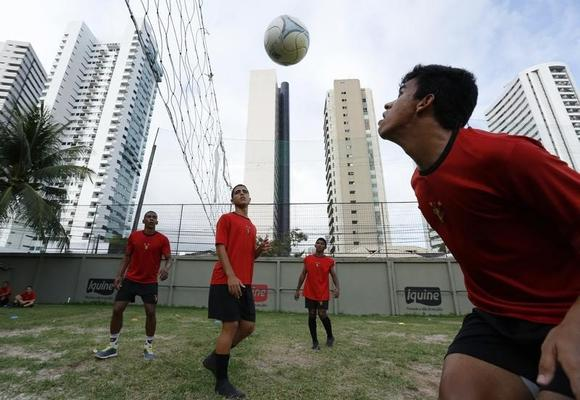 Youth kick and head the ball over a volleyball net with deft touches and neat flicks in Brazil's Sport Club Do Recife in Recife in this file photo taken on June 18, 2014. REUTERS/Ruben Sprich