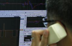 Сотрудник трейдинговой компании говорит по телефону перед экраном, на котором выведен график пары иены/доллар. Токио, 5 декабря 2014 года. Иена выросла к доллару и евро в понедельник, так как инвесторы напуганы конфликтом на Украине и перспективами выхода Греции из еврозоны. REUTERS/Yuya Shino