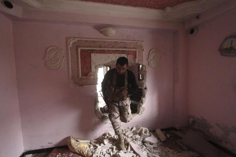 A rebel fighter of al-Jabha al-Shamiya (the Shamiya Front) moves through a hole in a wall inside a house north of Handarat camp in Aleppo, after the group said they took control of the area from forces loyal to Syria's President Bashar al-Assad, February 8, 2015. REUTERS/Hosam Katan