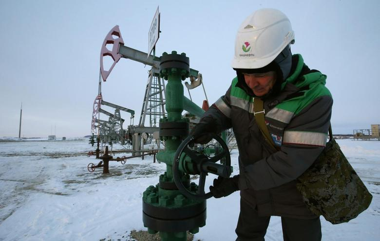 A worker checks the valve of an oil pipe at an oil field owned by Bashneft company near the village of Nikolo-Berezovka, northwest from Ufa, Bashkortostan, January 28, 2015. REUTERS/Sergei Karpukhin