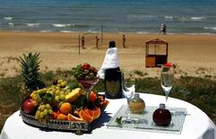 A platter of fruit and a bottle of Champagne is seen set up on a table by the beach of the Olympia Riviera resort in the town of Kyllini, some 285 kms southwest of Athens in this file photo taken on May 31, 2012.  REUTERS/Yannis Behrakis