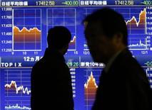Прохожие у брокерской конторы в Токио. 10 декабря 2014 года. Азиатские фондовые рынки завершили торги среды разнонаправленно под влиянием локальных факторов. REUTERS/Issei Kato