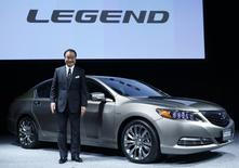 """Honda Motor Co's President and Chief Executive Officer Takanobu Ito poses with the company's renewal hybrid sedan car """"Legend"""" during an unveiling event in Tokyo in this November 10, 2014 file photo. REUTERS/Yuya Shino/Files"""