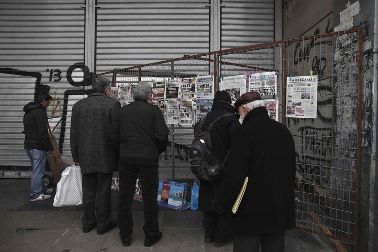 People read newspaper headlines in central Athens, February 12, 2015.  REUTERS/ Alkis Konstantinidis