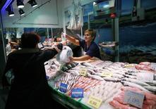 El Índice de los Precios de Consumo (IPC) español registró su séptima caída consecutiva en enero y registró una tasa interanual del -1,3 por ciento agravada por la caída de los precios de los carburantes, según datos divulgados el viernes por el Instituto Nacional de Estadística. En la imagen, una pescadera en un mercado del centro de Madrid, el 13 de noviembre de 2014. REUTERS/Andrea Comas