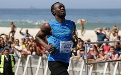 "Jamaican Olympic gold medallist Usain Bolt runs after winning the ""Mano a Mano"" men's 100 meters challenge on Copacabana beach in Rio de Janeiro August 17, 2014. REUTERS/Sergio Moraes"
