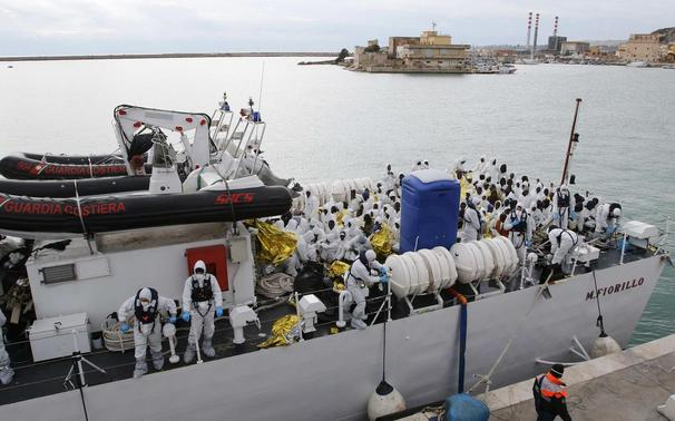 Migrants sit on the 'Fiorillo' Coast Guard vessel as they arrive at the Porto Empedocle harbour February 14, 2015. REUTERS-Antonio Parrinello