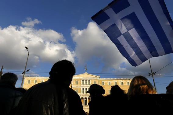 People are silhouetted as a Greek national flag flutters during an anti-austerity pro-government demonstration in front of the parliament in Athens February 15, 2015.  REUTERS-Yannis Behrakis